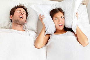 Snoring Man woman covering her ears with pillow